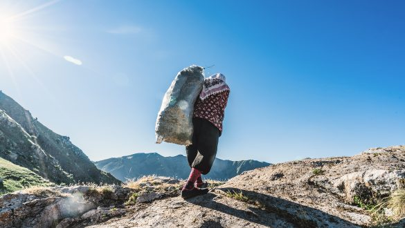 Woman carrying a bag of fresh cut grass up a steep hill