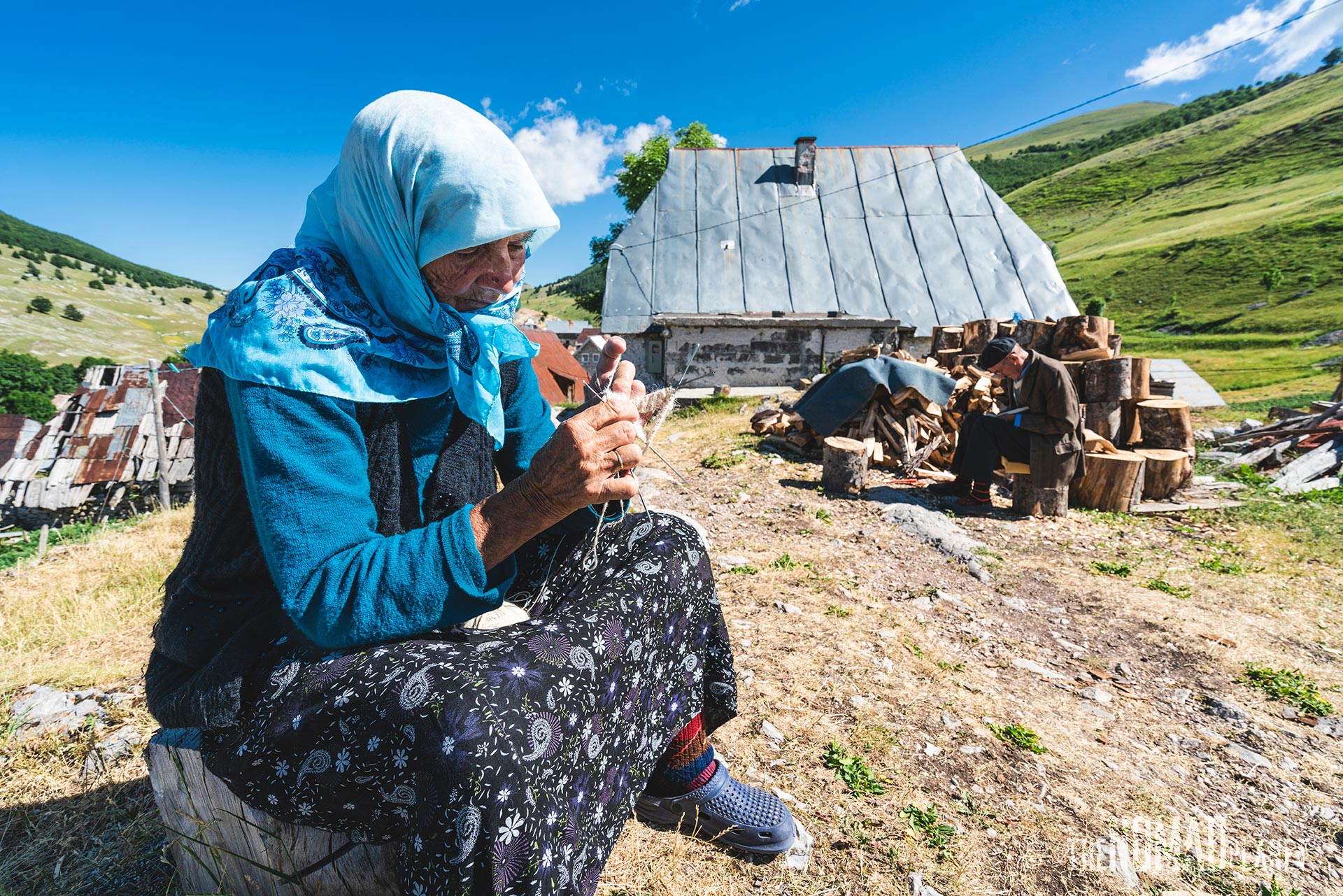 Village elders of Lukomir making wooden spoons and woolen socks for tourists in their backyard